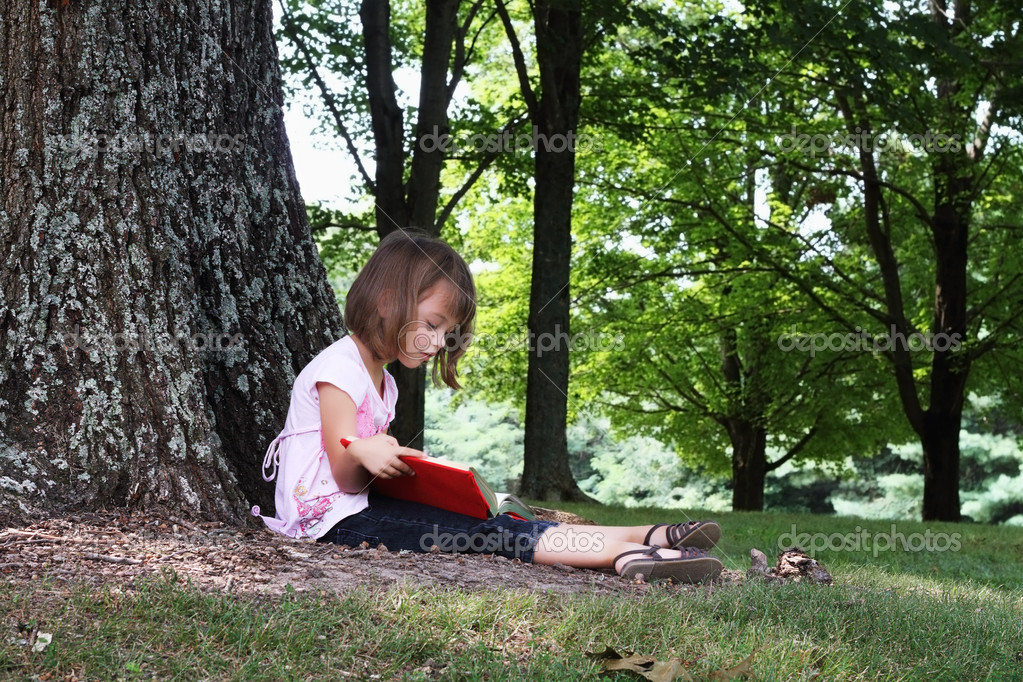 Little girl sits outdoors under a large oak tree and reads a book. — Stok fotoğraf #6249219