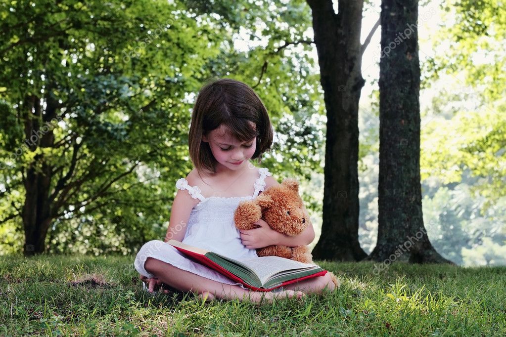 Girl reading outdoors to her little teddy bear.  Stock Photo #6249251
