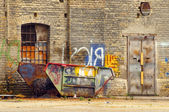 Old damaged container at the backyard of industrial building — Stock Photo