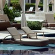 Reclining chairs in pool of luxury tropical resort — Stock Photo #5625602