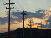 деревянные и стальные власти полюса на закате в стране — Стоковое фото