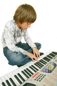 Cute kid playing piano, isolated — 图库照片