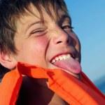 Portrait of playful cute boy showing tongue — Stock Photo