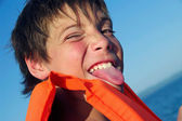 Portrait of playful cute boy showing tongue — Stock Photo