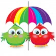 Two cartoon sparrow under the colorful umbrella — Vettoriali Stock