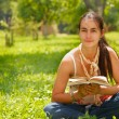Young woman reading a book outdoors. — Stock Photo