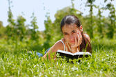 Young attractive woman reading a book and lying on a grass — Stock Photo