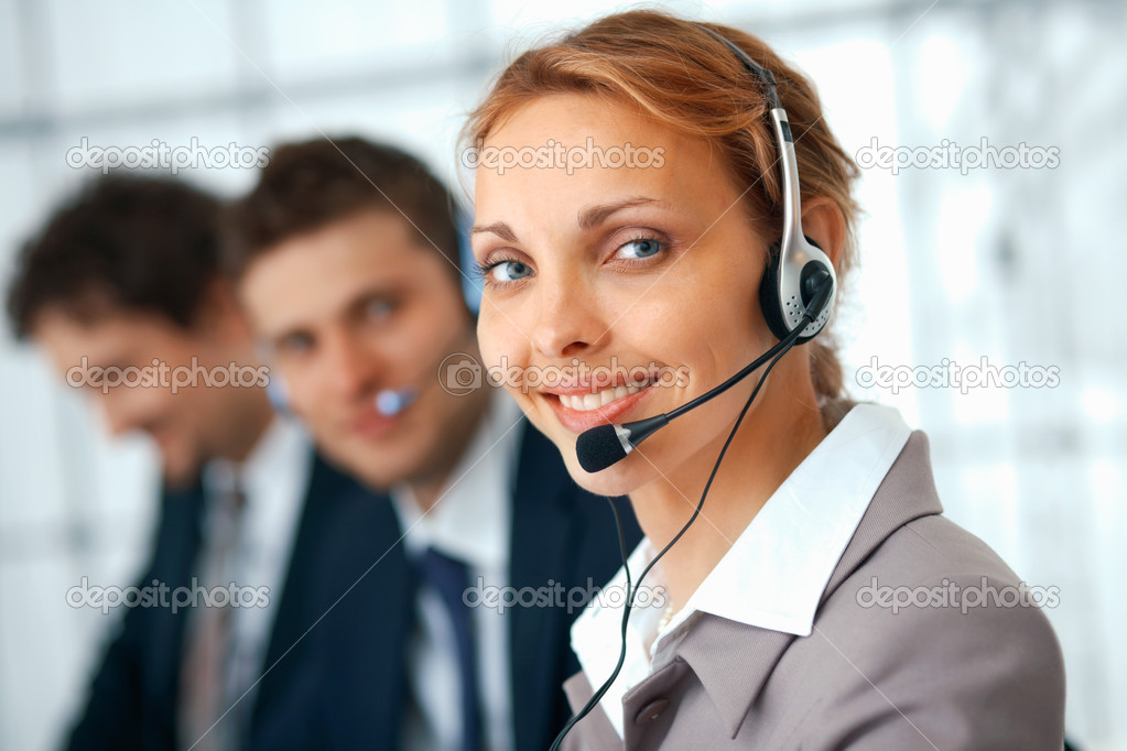 Closeup of a businesswoman with headset, her colleagues at the background.  Stock Photo #5571229