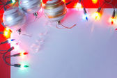 New Christmas baubles border with holiday lights. — Stock Photo
