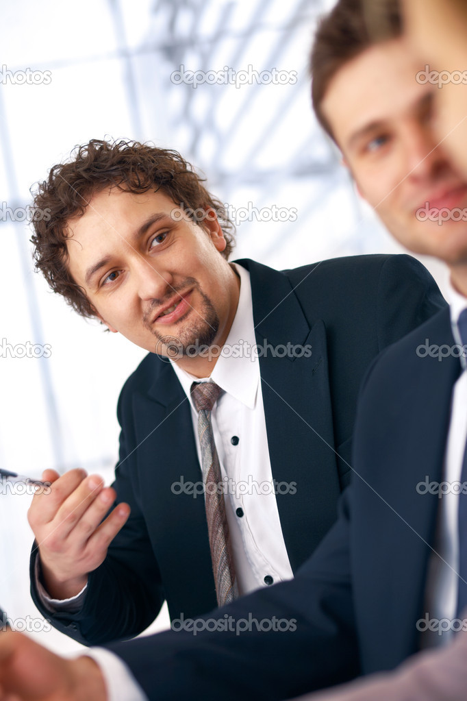 Young smiling businessman on the meeting looking and listening to partners.  Stock Photo #5971111