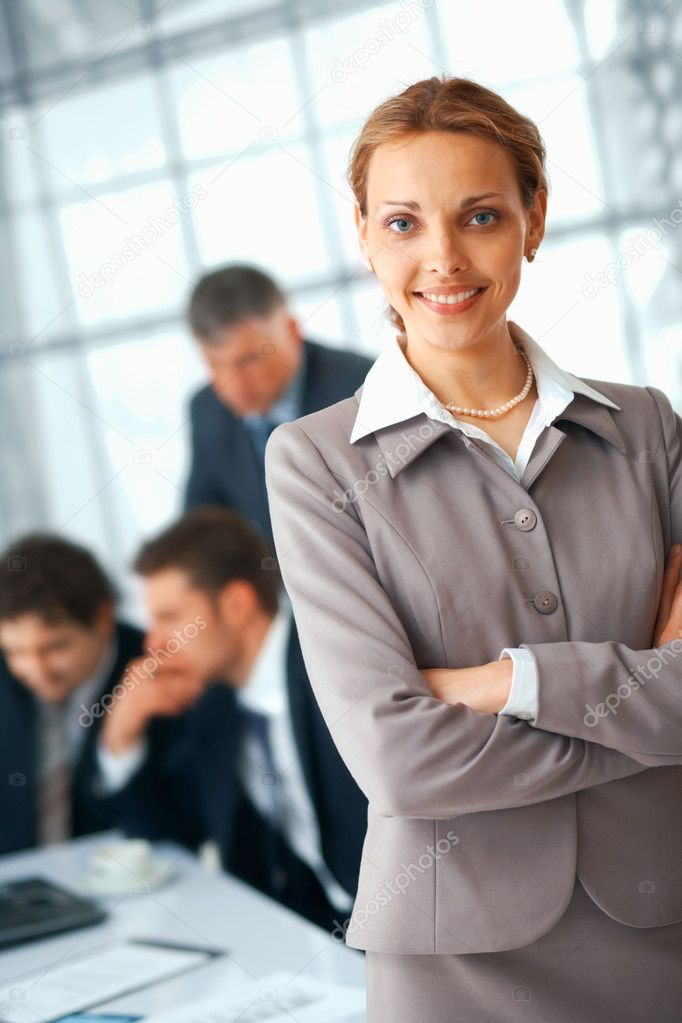 Young businesswoman standing with folded hands, her colleagues at the background. — Stock Photo #5971913