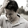 Sad and stressed young asian male — Stock Photo