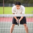 Asian male playing tennis — Stock fotografie