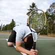 Sad tennis player after defeat - Stock Photo