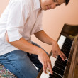 Asian playing piano — Stockfoto