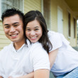 Asian couple in front of their house — Stock Photo