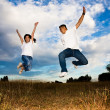 Asian couple jumping for joy — Stock Photo