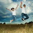 Asian couple jumping in joy - Stock Photo