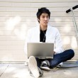 Young casual asian man with laptop — Stock Photo