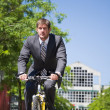 Caucasian businessman riding a bicycle — Stock Photo