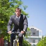 Caucasian businessman riding a bicycle — Stock Photo