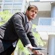 Caucasian businessman riding a bike — Stock Photo