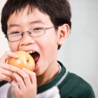 Stock Photo: A boy eating an apple