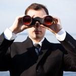 Caucasian businessman with binoculars — Stock Photo