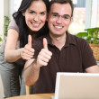 Happy couple giving thumbs up - Stock Photo