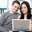 Happy couple browsing internet at home — Stock Photo