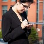 Hispanic businesswoman texting — Stock Photo