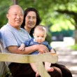 Child and grandparents in a park - Stock Photo