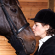 Senior woman kissing her horse — Stock Photo #5568381