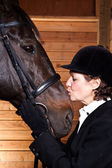 Senior woman kissing her horse — Stock Photo