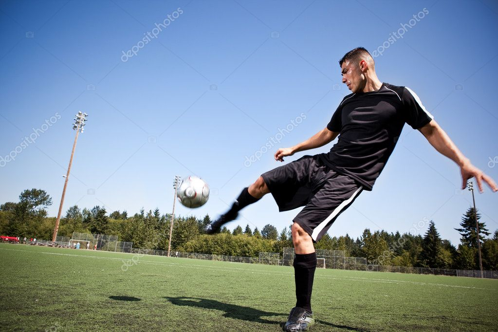 A shot of a hispanic soccer or football player kicking a ball — Stock Photo #5566920