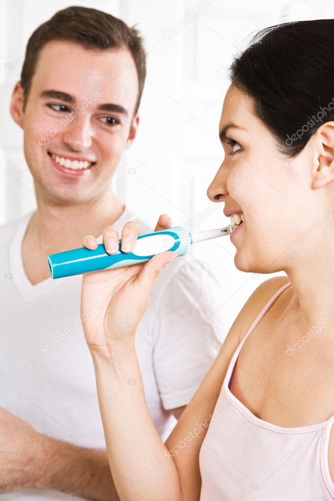 A beautiful interracial couple in the bathroom brushing teeth — Stock Photo #5567908