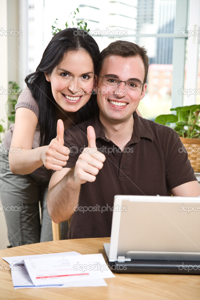 A happy couple paying bills by using online banking at home giving thumbs up — Stock Photo #5567949