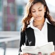 Black businesswoman reading newspaper — Stock Photo