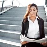Black businesswoman reading newspaper — Stock Photo