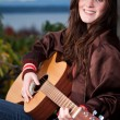Beautiful teenager playing guitar — Stock Photo