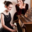 Mother and daughter playing piano — Stock Photo #5654222