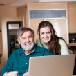 Teenage girl with grandpa using laptop — Stock Photo #5654919