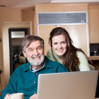 Teenage girl with grandpa using laptop - Stock Photo