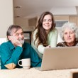 Teenage girl with grandparents using laptop - Stock Photo