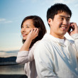 Asian couple on the phone - Stock Photo