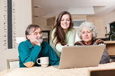 Teenage girl with grandparents using laptop — Stock Photo