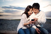 Asian couple texting — Stock Photo