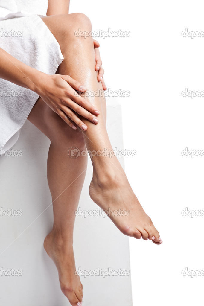 An isolated shot of a beautiful black woman applying  lotion on her legs  Stock Photo #5653774