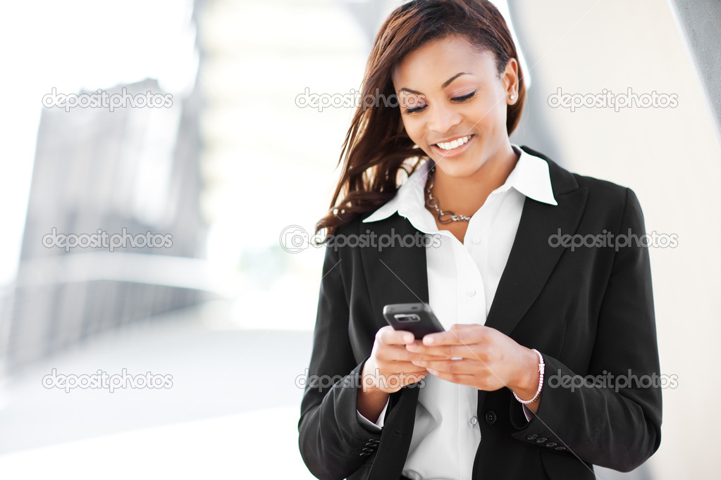 A shot of a beautiful black businesswoman texting — Stock Photo #5653902