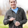 Mixed race man holding water bottle — Stock Photo